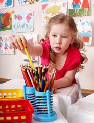 Child  with colour pencil in preschool.