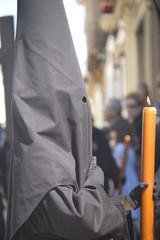 nazareno de perfil sujetando vela en Semana Santa