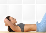 A young and sporty female is doing abs exercise poster