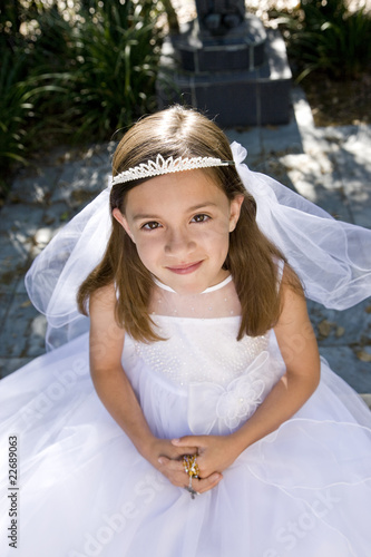 Young girl in white dress and veil outdoors