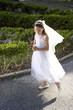 Beautiful child in white dress holding rosary