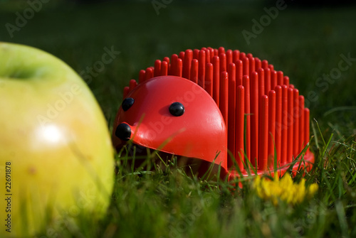 red plastic penholder hedgehog finds a natural apple