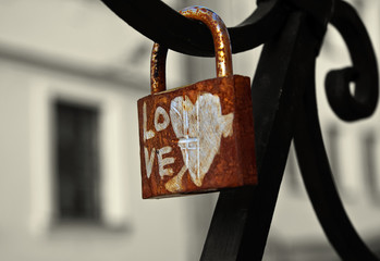 Old padlock hanging on a fence with writing Love
