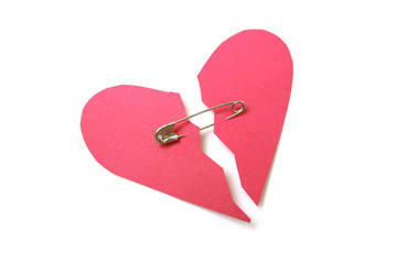 Red paper heart torn in half secured with safety pin