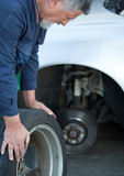 mechanic changing a wheel of a modern car (color toned image) poster