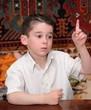 Serious cute little boy raises his finger