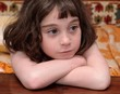Serious cute little girl rests her head on crossed arms