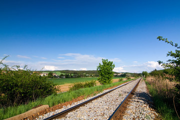 Spring countryside with railway and blue sky