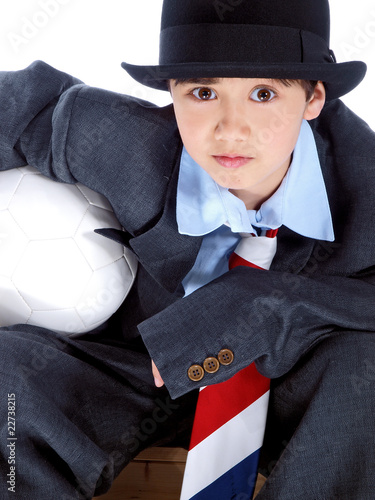 child in business suit holding a soccer ball