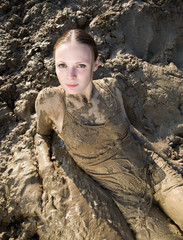 Sexy woman lying in the mud