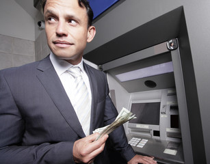 Businessman holding money by an atm machine