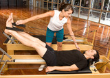 Girl assisting man during pilates