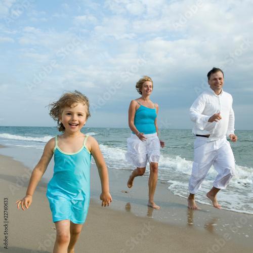 Happy family running at the beach