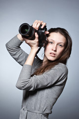 Unusual portrait of beautiful female photographer shooting