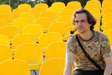 Lonely man among empty yellow plastic chairs at stadium