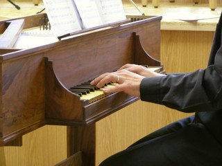 hands playing an harpsichord keyboard