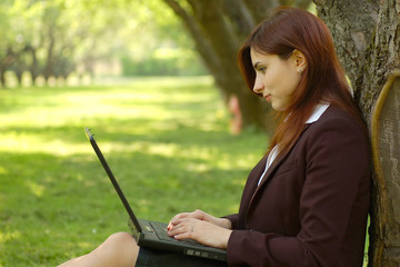Young business woman working on the laptop in the park