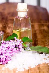 bath and spa items (salt, oil, lilac) on wooden background