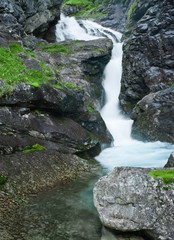 Small waterfall in black rocks. Northern Norway
