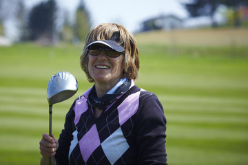 portrait of a golfer woman holding iron and smiling.