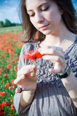 donna che stacca i petali di un fiore