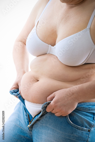 Overweight lady attempting to fasten too small jeans