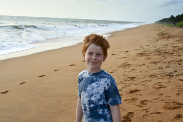 child with red hair at the beach near Colombo