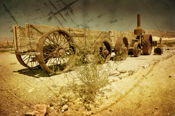 An old wagon in the Death Valley in grunge and retro style