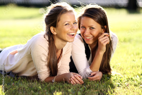 Young beautiful twins of sister lays on green field