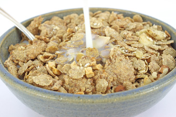 Banana and nut granola cereal with milk pouring