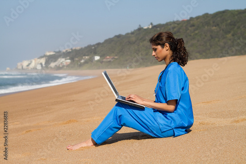 intern using laptop on beach
