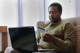 muž pomocí kreditní karty nakupovat online s laptop