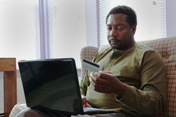 Man Using Credit Card Shopping Online With Laptop