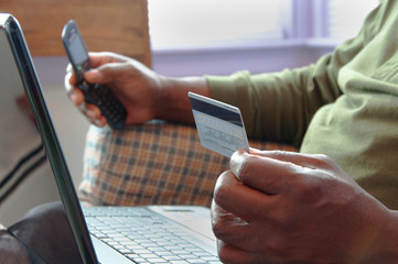 Man With Laptop Using Credit Card and Cellphone