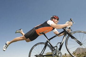 Male cyclist balances his stomach on bicycle seat