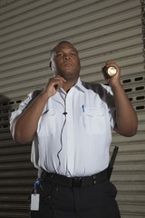Security guard patrols with torch