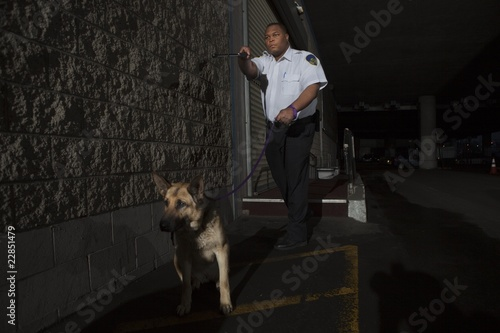 Security guard in alleyway pursuit with guard dog