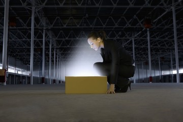 Woman peers into yellow box shining bright light