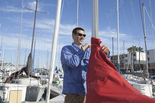 Young man securing sail of boat