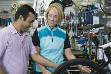 Bike shop assistant helps female cyclist