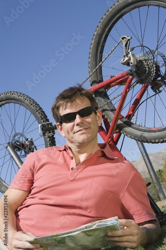 Mature man lies with ma, bike upside down