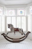 Antique rocking horse in bay window with stained glass, London