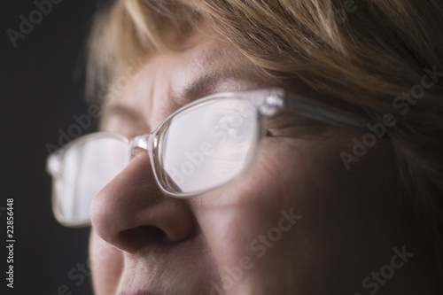 Mature woman with light reflecting on reading glasses