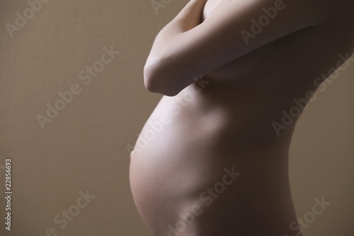 Pregnant woman stands with arm  across her chest