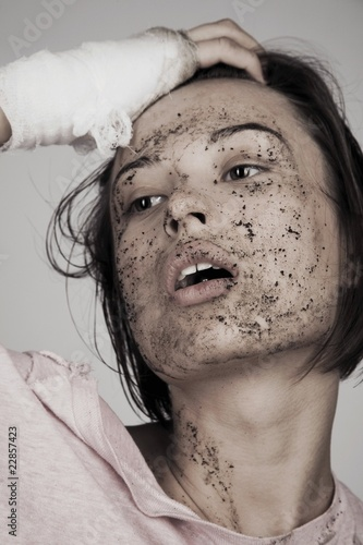Young woman with bandage and muddy face