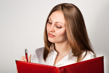 Pretty young woman writing in notice book
