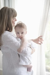 Mother stands looking through window while holding a baby boy