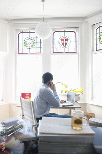 Businessman works from desk in bay window