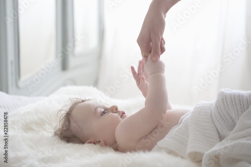 Baby boy reaches for mother's hand