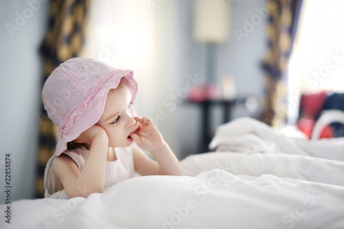 Thoughtful toddler girl in nice hat